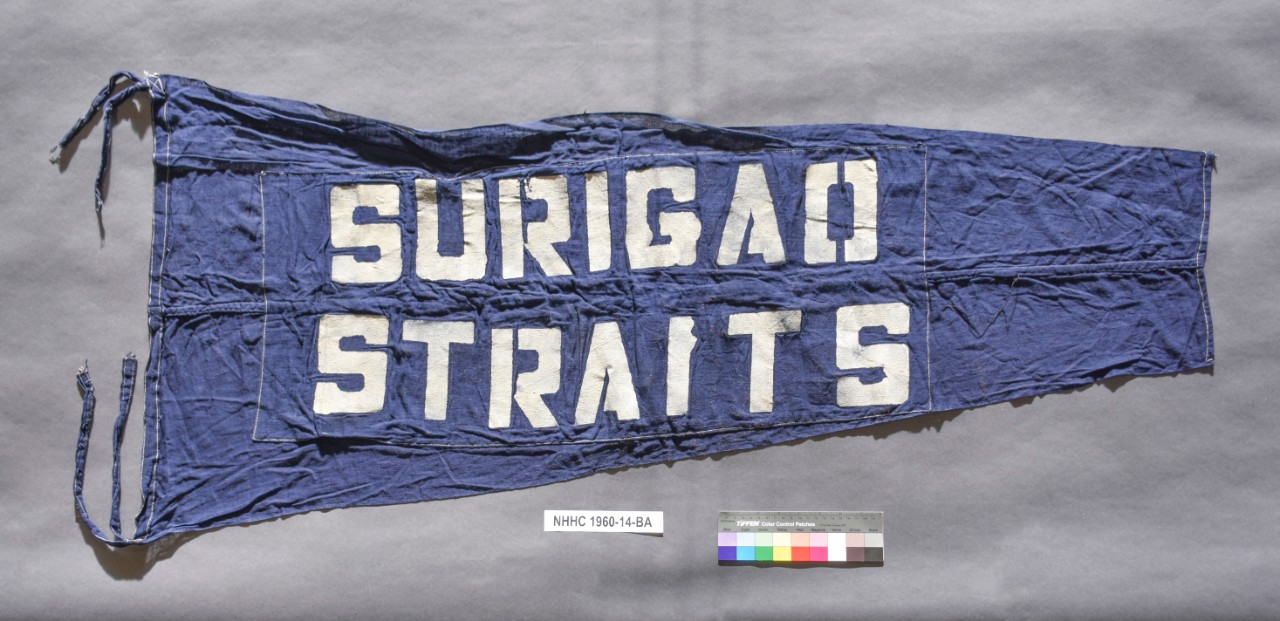<p>Blue Pennant with white letters Surigao Straits. Streamers at either end of the hoist</p>