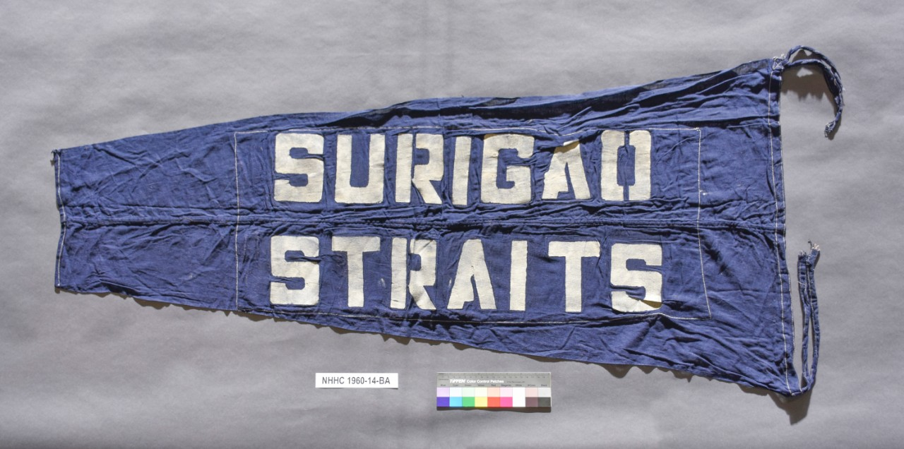 <p>Blue Pennant with streamers at either end of hoist. &quot;Surigao Straits&quot; written in white letters</p>