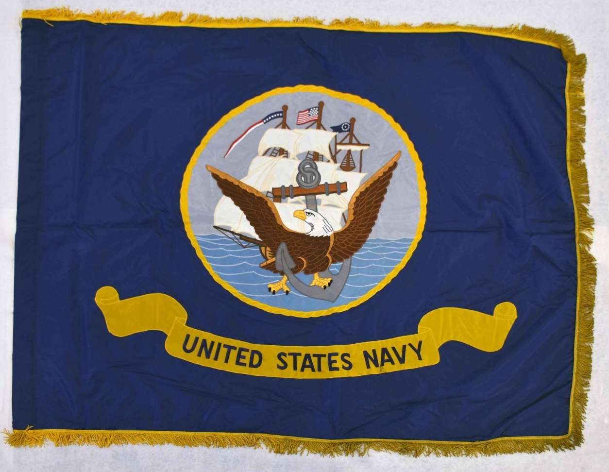 "<p>One US Navy flag. The flag is rectangular-shaped blue nylon edged with gold fringe. At the center of the flag is the seal of the US Navy with the eagle, anchor, and sailing ship above a banner with the words ""United States Navy."" There are smoke stains on the bottom right corner of the fly.</p>"