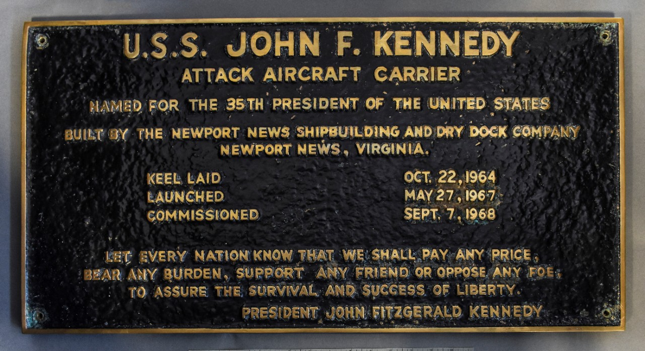 <p>Bronze plaque with builders information including keel laying, launching and commissioning for the attach aircraft carrier USS John F Kennedy. background painted black 4 bolt holes at each corner</p>
