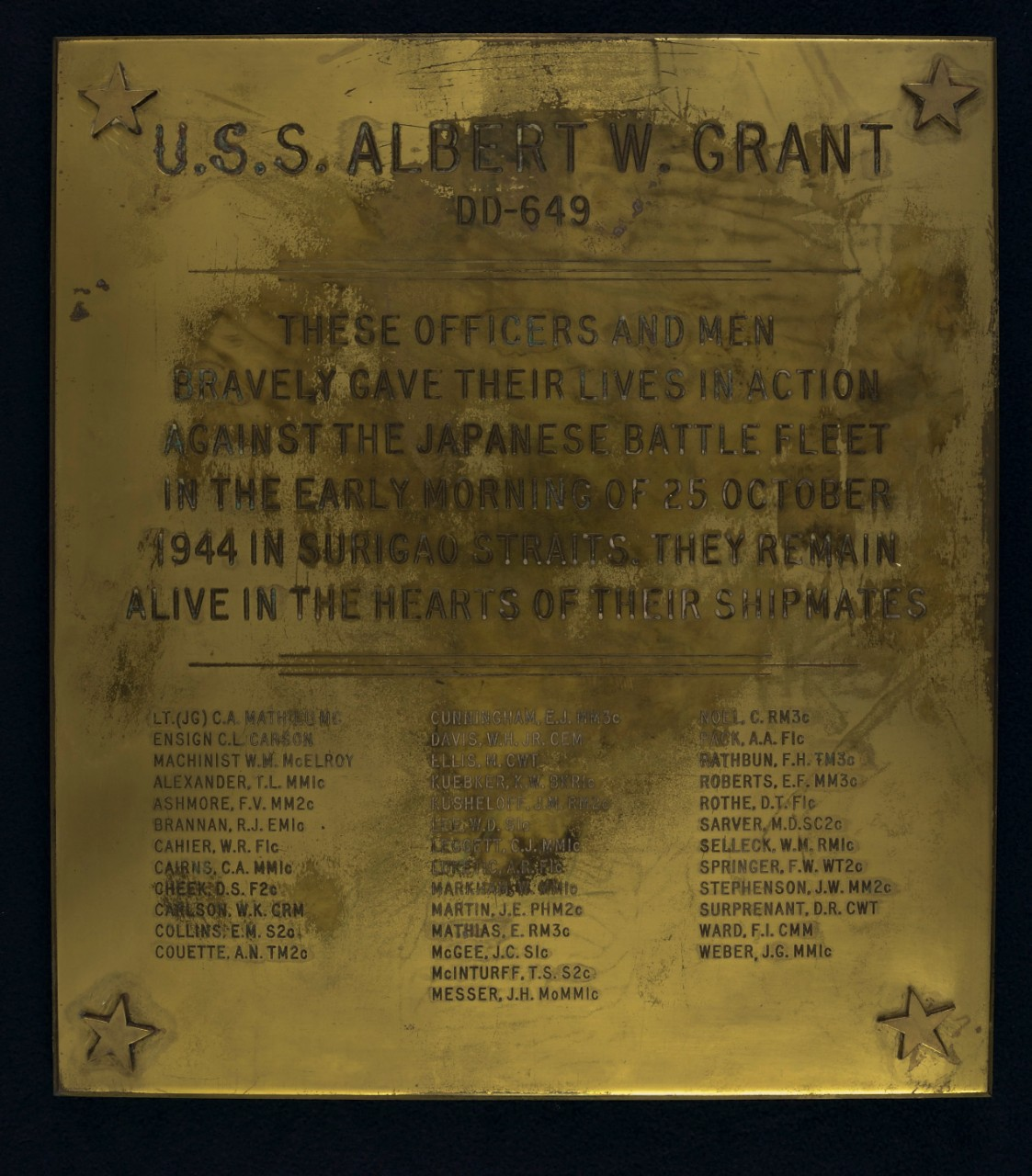 <p>Brass Plaque with a star at each corner, name of the ship and hull number with text marking the battle of Surigao Straits and names of those lost</p>