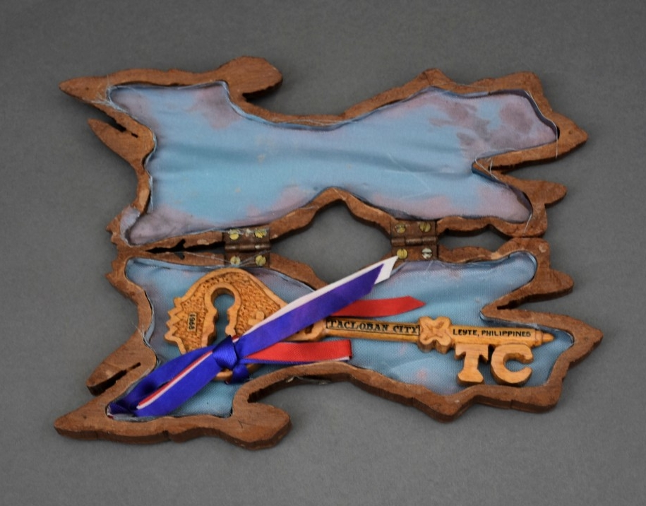 <p>Blue fabric glued to case carved in shape of Luzon.&nbsp; Interior housing wood carved key</p>
