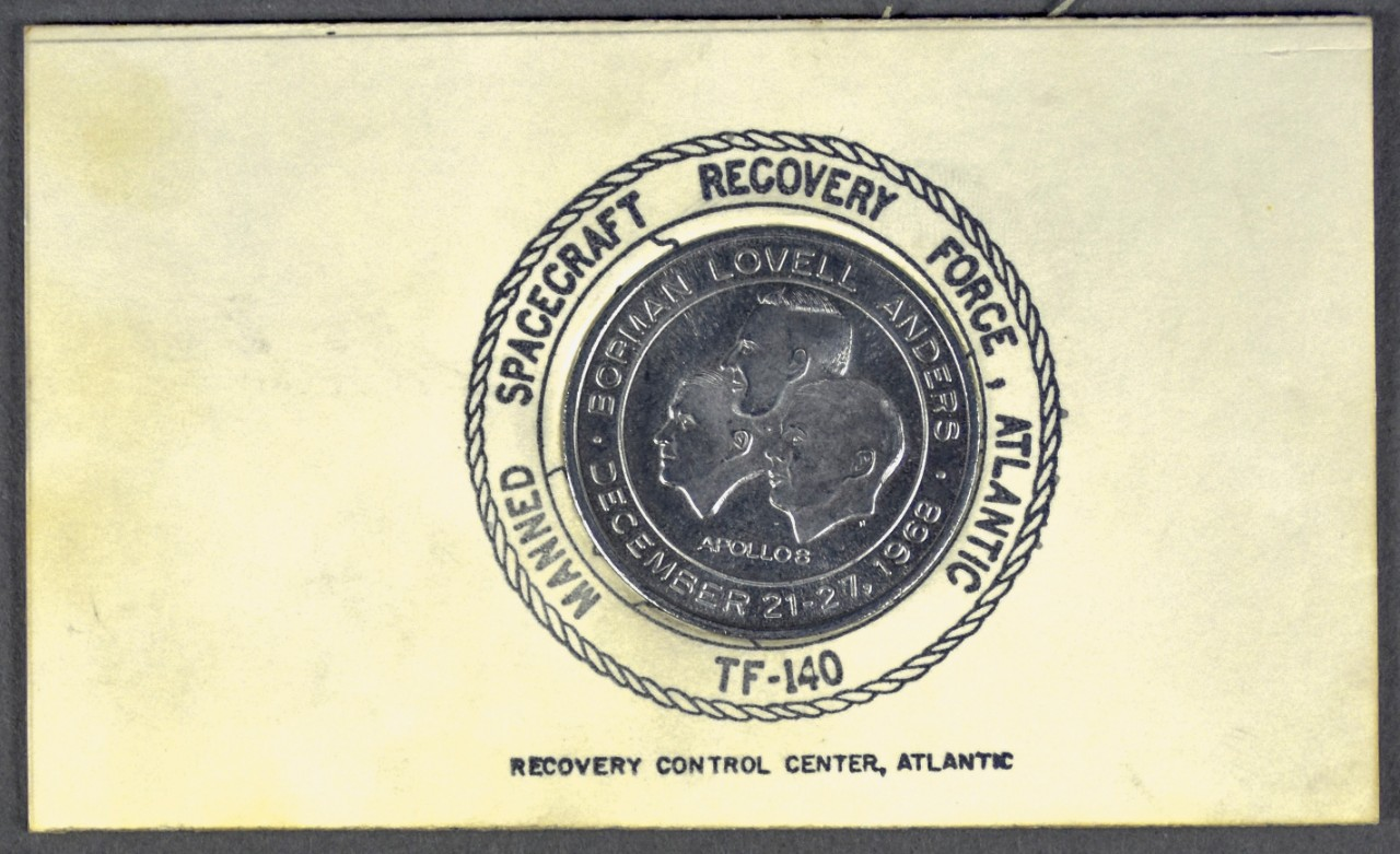 One commemorative coin from apollo 8 Recovery mounted on cardboard stamped with manned spacecraft recovery force atlantic