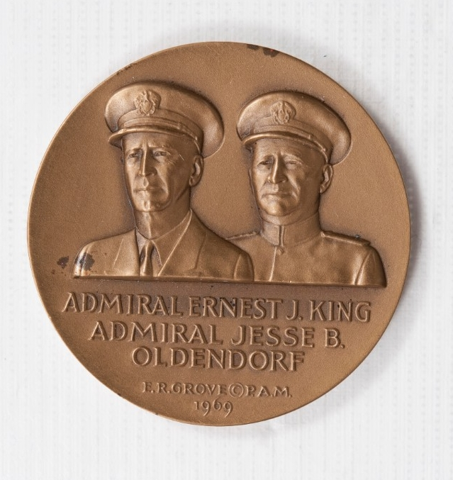 <p>Bronze coin Obverse is Busts of Admirals Oldendorf and King in Navy Uniforms and Hats with names below</p>