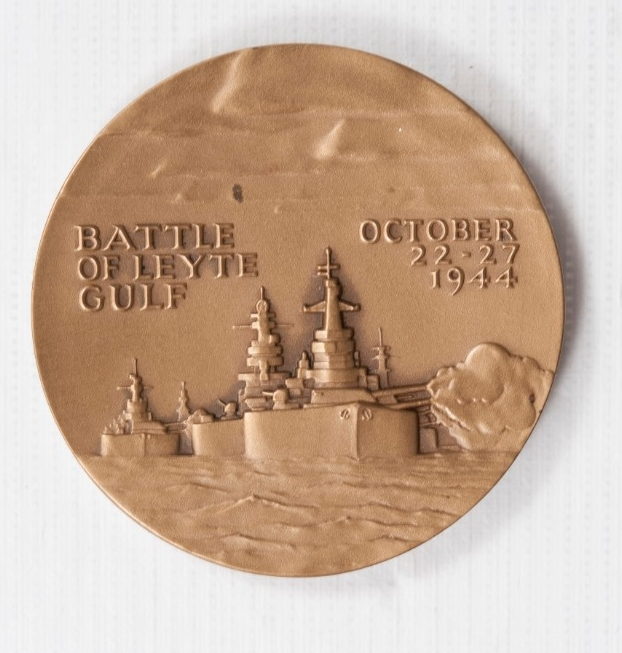 <p>Round Bronze with raised image of ships with Battle of Leyte Gulf October 22-27 1944 in raised letters</p>