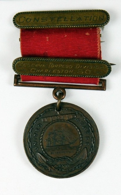 <p>Good Conduct planchet with red ribbon and two devices attached to ribbon, one with pin and clasp brooch</p>