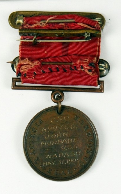 <p>Reverse of medal showing diffferent devices on ribbon and engraved planchet</p>