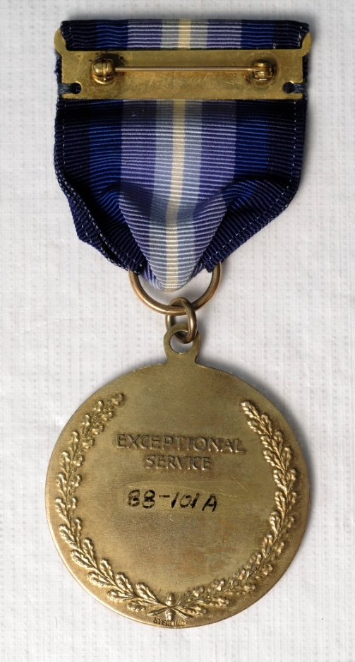 <p>One Type I NASA&nbsp;Distinguished Service Medal. Medal is sterling silver. Planchet is the official Seal of NASA with &quot;National Aeronautics and Space Administration/USA&quot; around the rim. The reverse is oak branches around the rim with &quot;Exceptional Service&quot; in raised letters. The planchet is attached with a suspension ring to a tapered ribbon. The colors of the ribbon are&nbsp;Navy blue, blue, purple, sky blue, and white. The pin and clasp is sewn to the ribbon.</p>