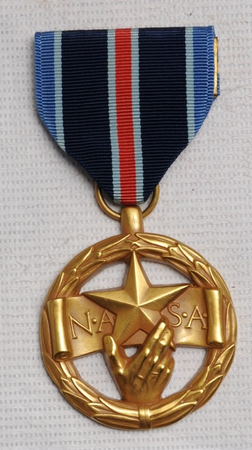 <p>&nbsp;The medal is gold in color and is the shape of a right hand holding a five-pointed star superimposed over a banner that reads, &quot;N.A.S.A.&quot; This is all surrounded by a wreath.&nbsp;</p>
