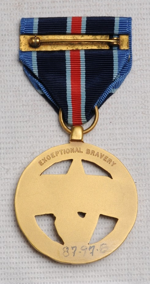 <p>Reverse of NASA Exceptional Bravery medal showing &quot;Esceptional Bravery&quot; engraved along the top and pin and clasp brooch.</p>