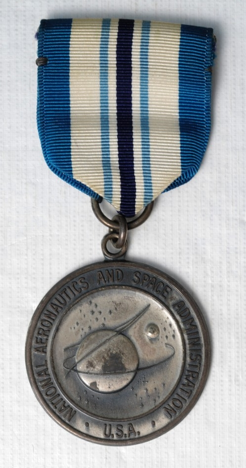 <p>One Type I NASA Exceptional Service Medal. Medal is sterling silver. Planchet is the official Seal of NASA with &quot;National Aeronautics and Space Administration/USA&quot; around the rim. The reverse is oak branches around the rim with &quot;Exceptional Service&quot; in raised letters. The planchet is attached with a suspension ring to a tapered ribbon. The colors of the ribbon are azure blue, white, sky blue, and Navy blue. The pin and clasp is sewn to the ribbon.</p>