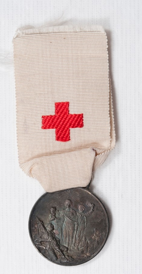 White ribbon with red cross and medallion marking earthquake relief in Italy 1909