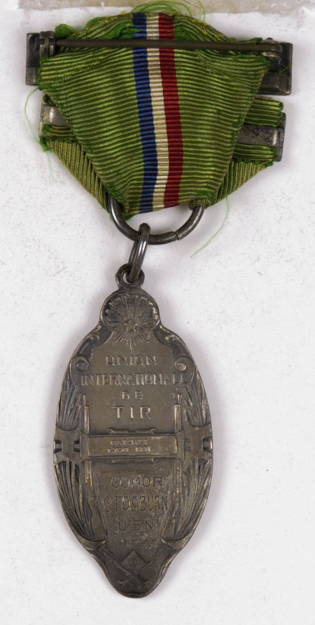 MEDAL-NRA INTERNATIONAL TEAM, UNION INTERNATIONALE DE TIR, MATCHES LYON 1921. THE MEDAL RIBBON IS GREEN WITH A CENTRAL STRIPE OF RED, WHITE AND BLUE.