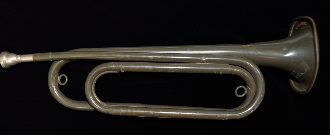 "One military-issued service bugle. Brass or copper alloy body painted gray. The body has a double twist shape and a white metal mouthpiece. The bell is stamped ""BUGLECRAFT INC./L.I. City, N.Y./U.S."""