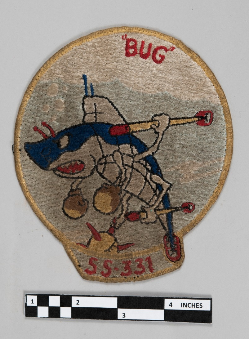 <p>Color patch with blue shark as submarine with boxing gloves, and arms holding mines and torpedoes. red lettering &quot;Bug&quot; and SS-331</p>