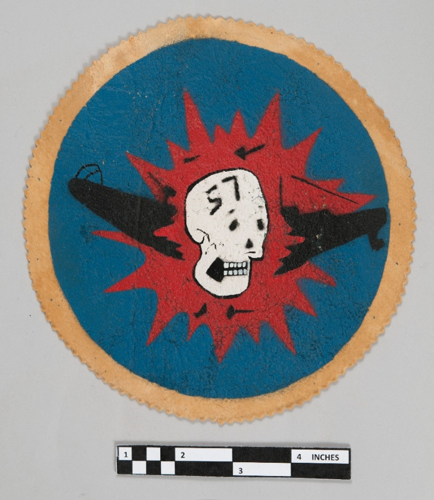<p>one hand painted insignia patch with skull over exploding submarine red black and blue on brown fabric</p>