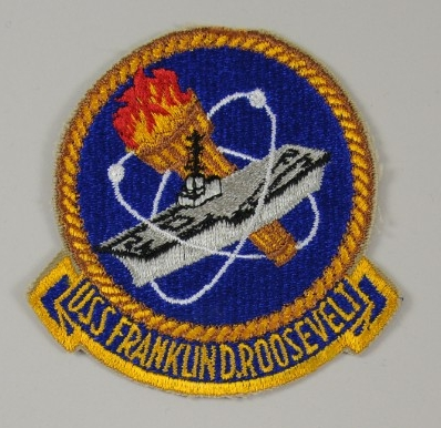 Patch with an aircraft carrier and a nuclear symbol and torch with USS Franklin D Roosevelt