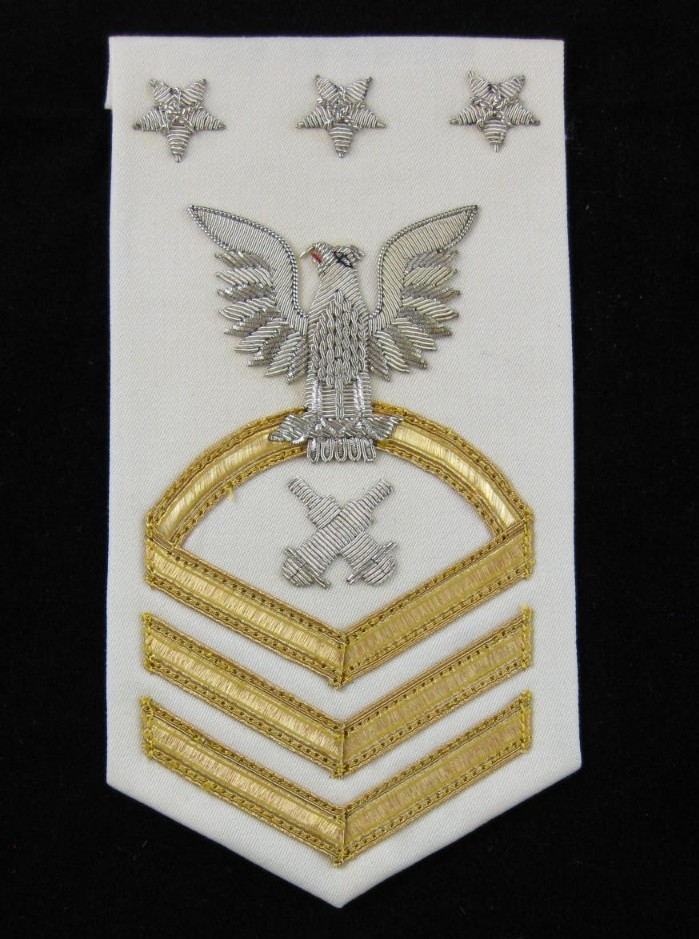 White and gold rating badge for Master Chief Petty Officer of the Navy