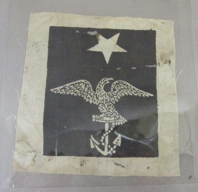 One white and black rating badge with eagle holding foul anchor and one white star above black field with white border