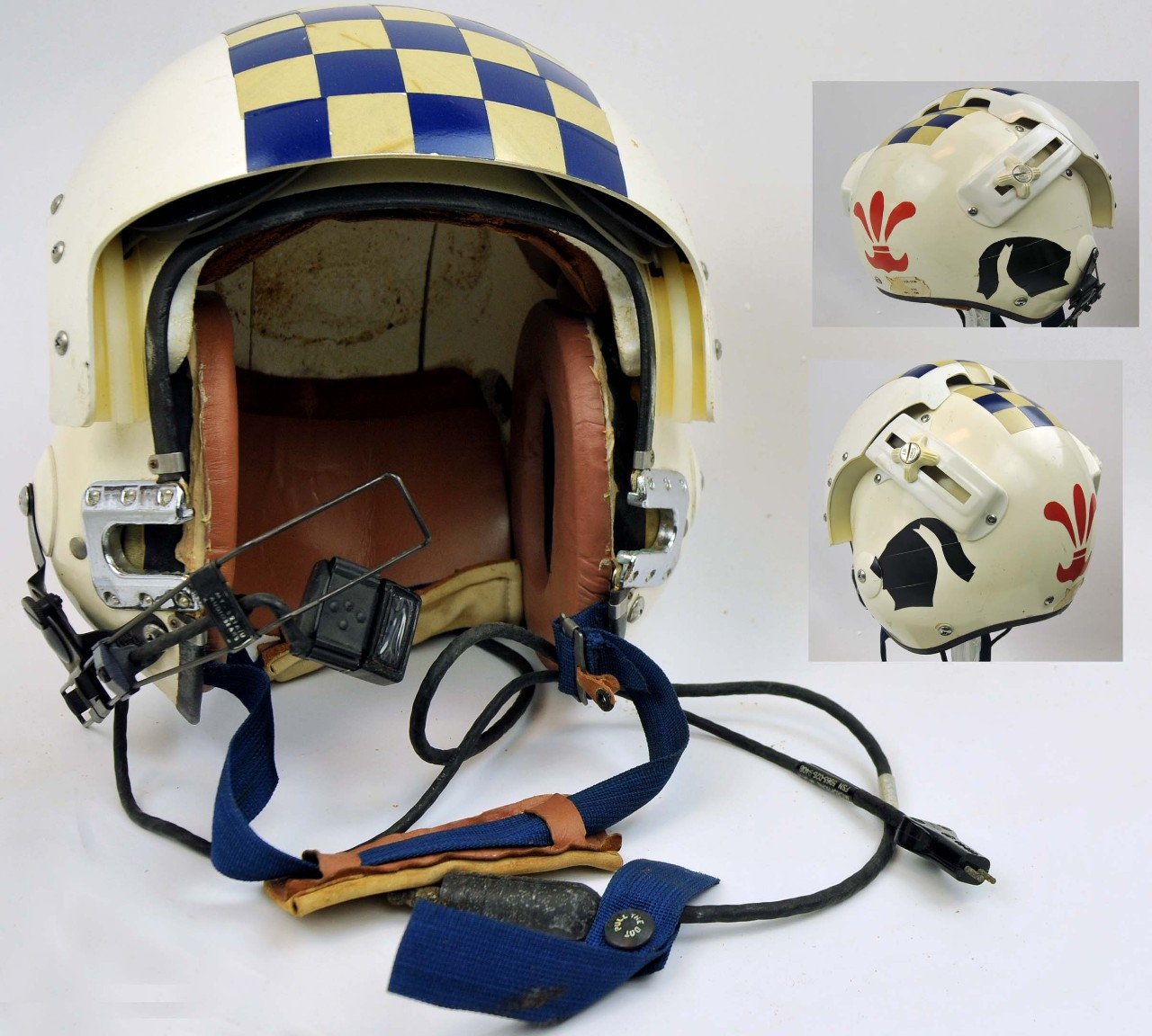 <p>One white flight helmet. The top and visor of the helmet have a square patch of blue and yellow squares in a checkboard pattern. The visor is adjustable along a track with two adjustment hand wheels on either side of the helmet. The part of the helmet that covers the ears, there is a black silhouette of a knight's helmet with trialing plume. At the back of the helmet is a red silhouette similar to a fleur-de-lis. At the front of the helmet is an adjustable blue strap with chin pad. There is an adjustable metal arm protruding from the right front sight that supports a black plastic square microphone. There is a black cord attached to the microphone that ends in a plug. The interior of the helmet is lined with reddish-brown foam.</p>
