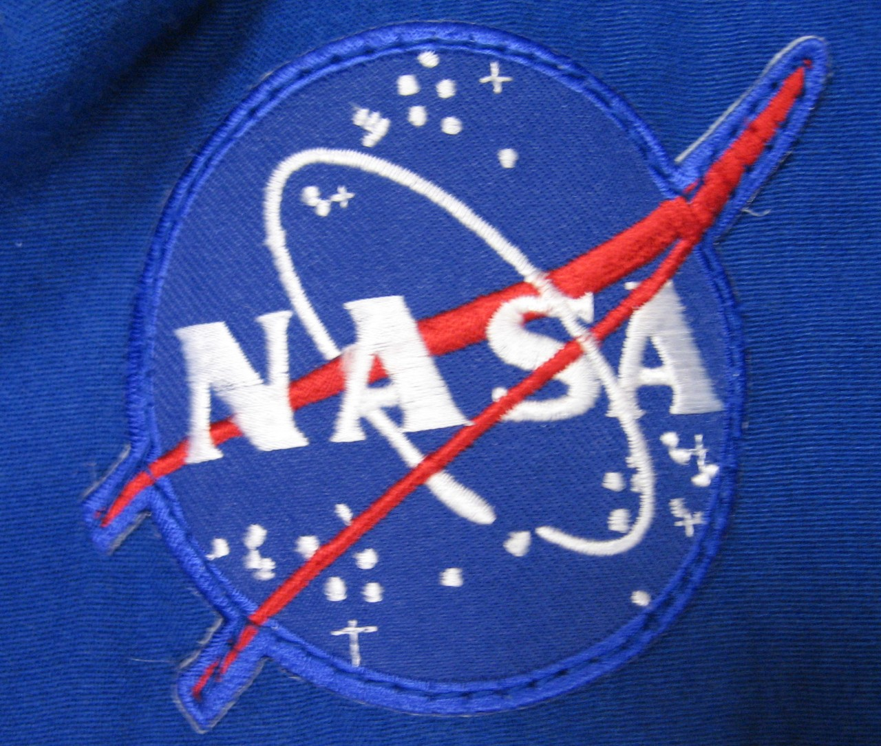 NASA patch on right chest of NASA coveralls.