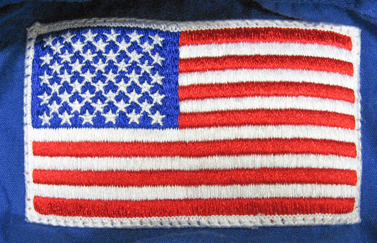 American flag patch on left shoulder of NASA coveralls.
