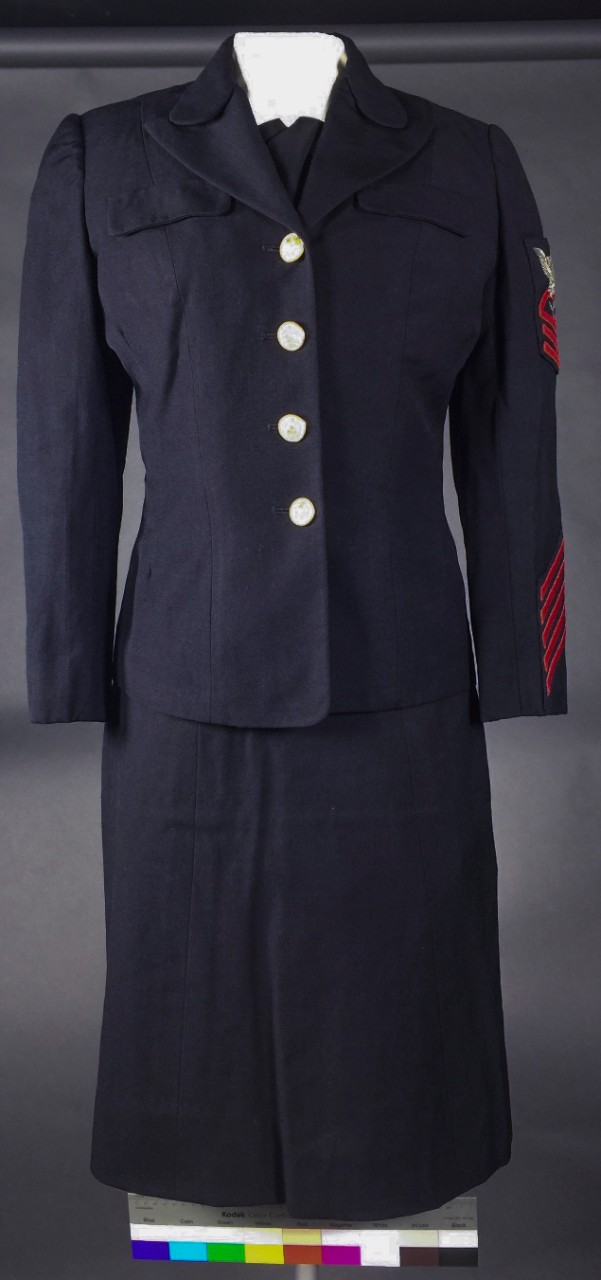 Dark blue uniform including service coat, skirt, and black tie. Rating on arm indicates Yeoman Chief Petty Officer with 20 years of service.