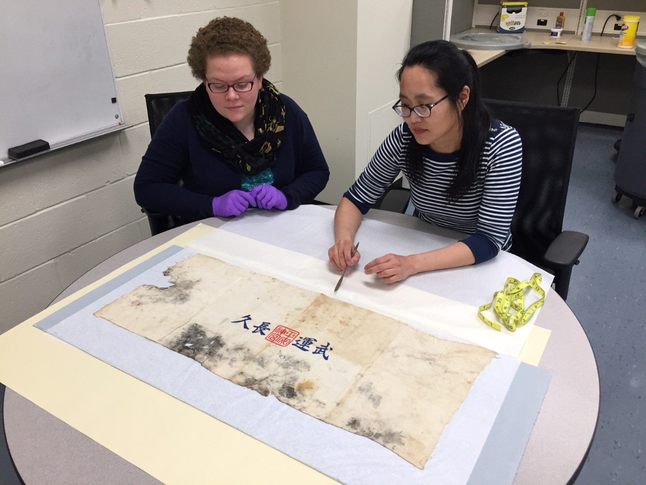 Two conservators examine a Japanese prayer towel.