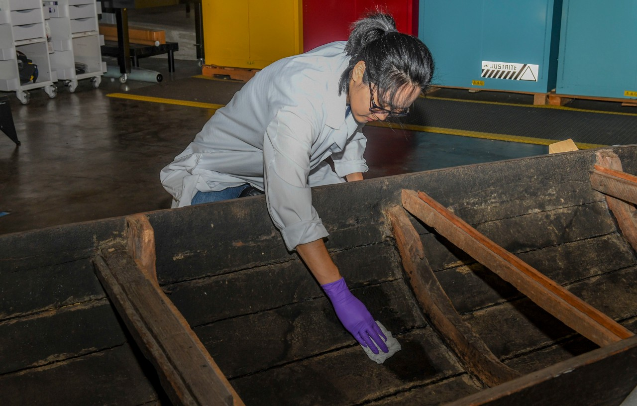 <p>Yoonjo Lee, senior conservator deputy at the Conservation Branch, Collection Management Facility, Naval History and Heritage Command, uses distilled water to clean the planks of a Vietnamese watercraft called a sampan.</p>
