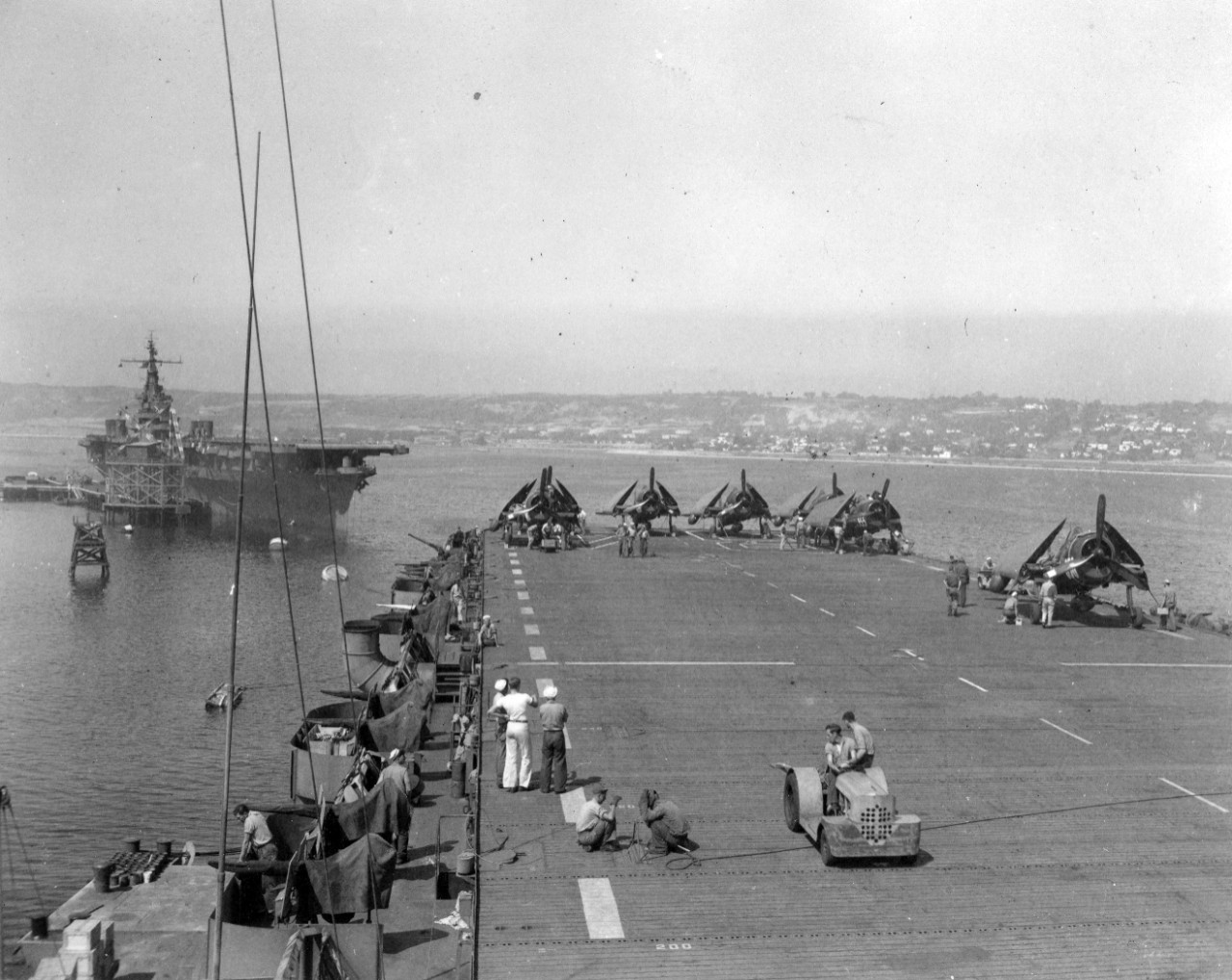 Collection of 14 photos related to the naval service of Frances Goodwin during WWII. The photos contain images of actives onboard USS Shamrock Bay (CVE-84), specifically Crossing the Line Ceremonies and loading aircraft onto the ship while at North Island, San Diego, CA, September 14, 1945 (V-J Day). The collection also includes a crew photo celebrating and cheering the end of WWII after the official announcement. It is not known if Goodwin is in the photo of the crew. There is also an undated image of USS PT-10 in New York Harbor (Statue of Liberty is in the background). Also in the collection is a typed narrative dated September 7, 1945 on the history of the WWII service of USS Shamrock Bay.