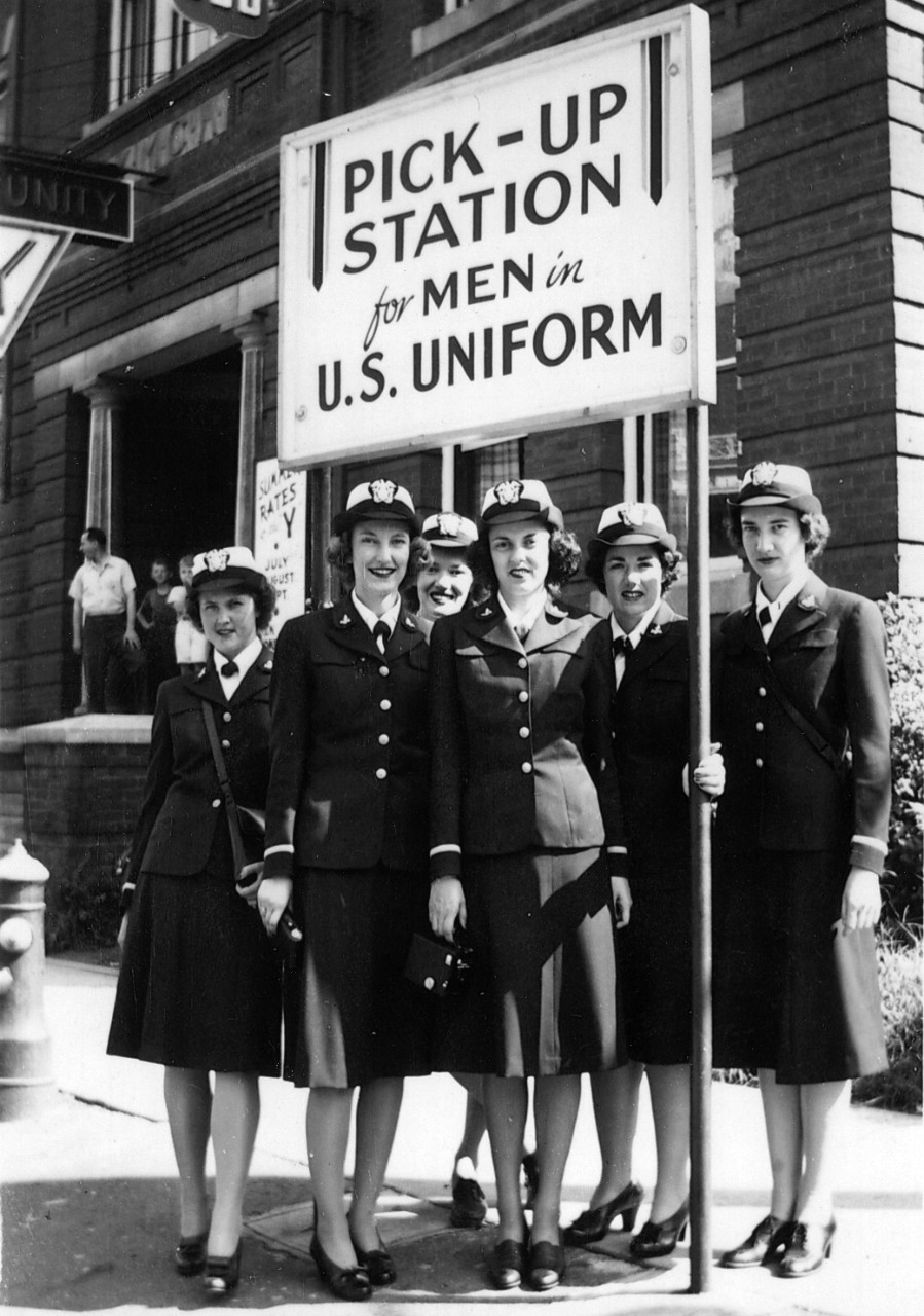 "One black and white copy print showing WAVES in front of a sign reading ""Pick-Up Station for Men in U.S. Uniform,"" donated by Lindy Ader in 2008 and transferred from Curator Branch. Donor's mother, Cicely Frances Peeples, is at far right in photo. Photo possibly taken in Washington, D.C."