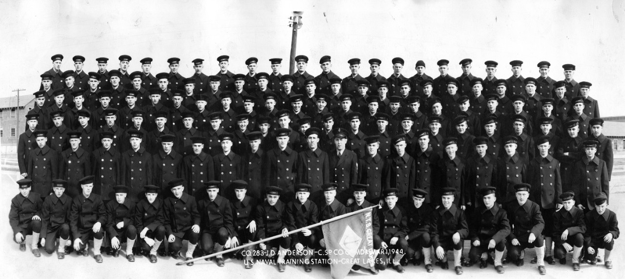 "Collection of 21 oversized photographs related to the WWII naval service of John D. Anderson as a ""Boot"" Company Commander at Naval Training Center, Great Lakes, IL. The images consist of Great Lakes recruit (""boot"") companies from 1942-1945. CSp John D. Anderson is in most of the photos as Company Commander. Each image includes a company roster with member's names. Below is a listing of each company with the date. Also included in the collection is a photo of Great Lakes Tenth Regiment during a Captain's Inspection on 30 September 1944."