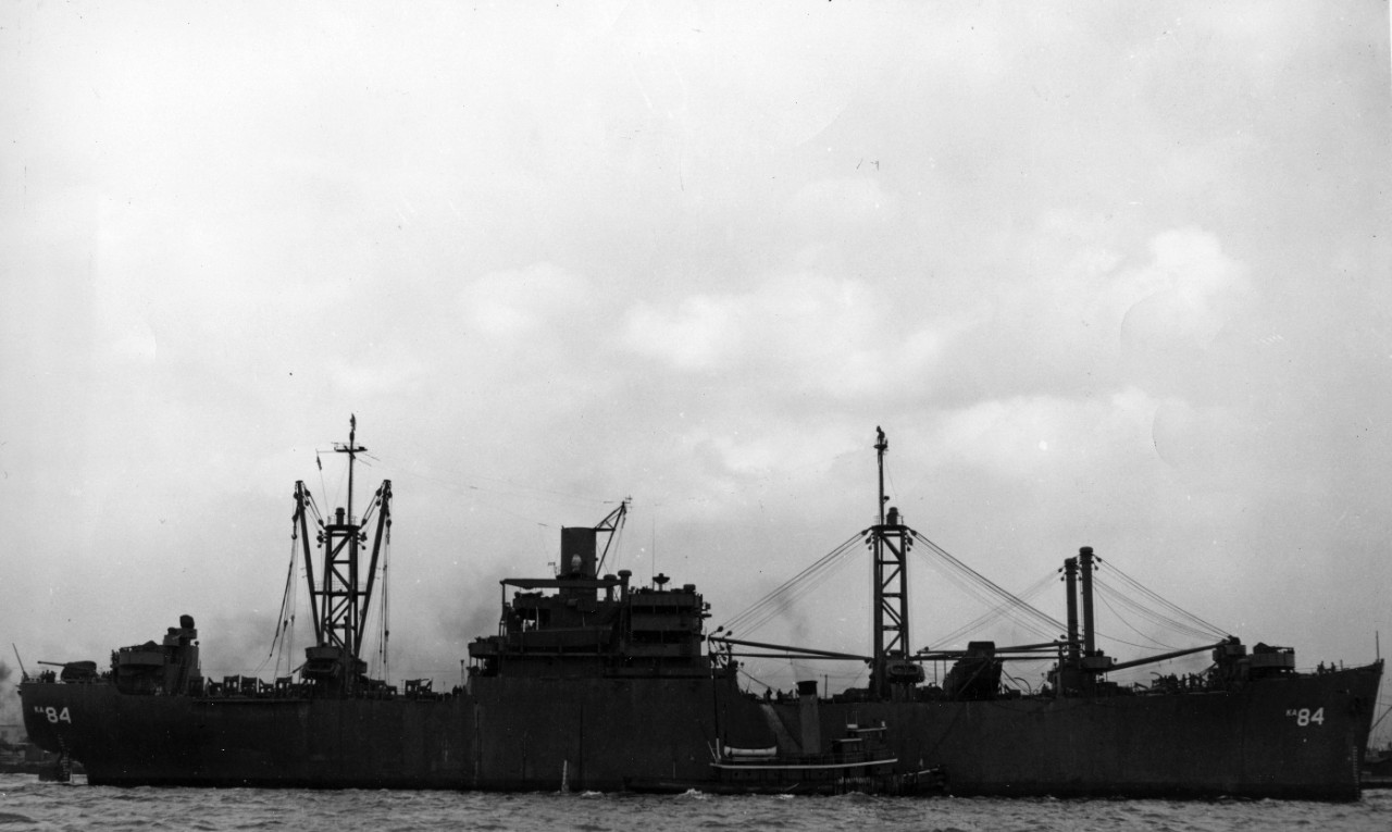 Starboard broadside view of attack cargo ship USS Waukesha (AKA-84) being assisted by a tugboat