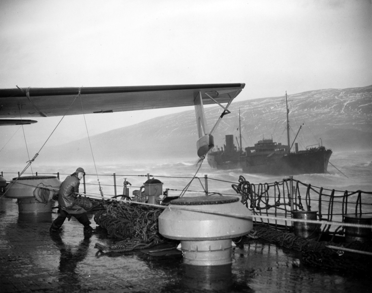The crew of a seaplane tender struggling to secure seaplanes during a storm off the coast of Hvalfjordur, Iceland. From the VADM Robert C. Giffen Photo Collection.
