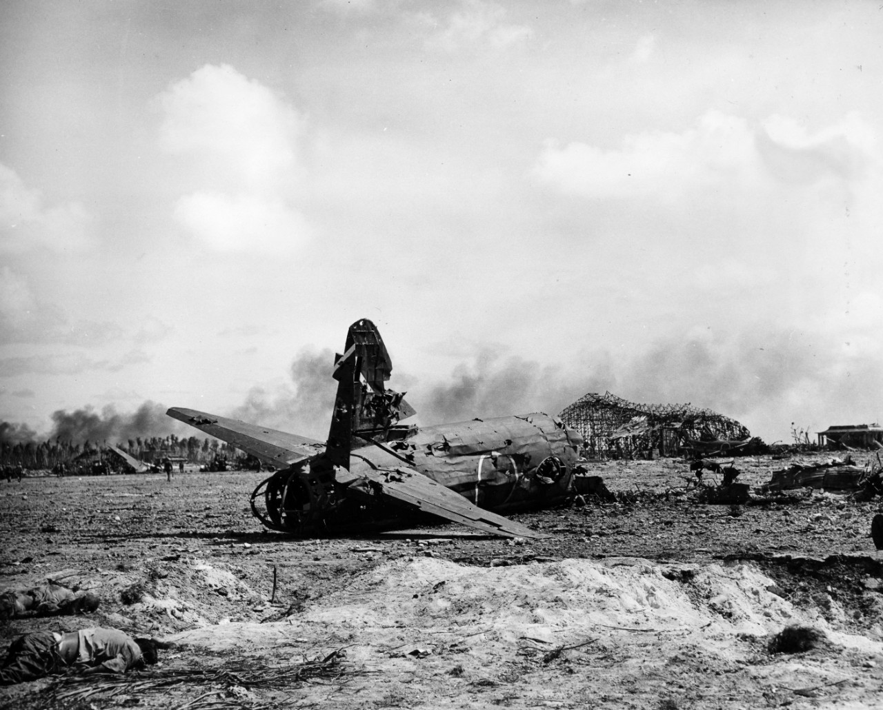 "Airfield destruction and wrecked aircraft, ""Zero"" and Betty"" types on the island of Roi in the Kwakjalein after invasion, February 1944. From the VADM Robert C. Giffen Photo Collection."