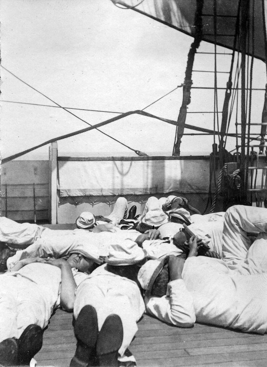 US Naval Academy midshipmen resting on the deck of a training vessel. The midshipmen are part of the Naval Academy class of 1905. Image is from the Clarence Grace Collection.