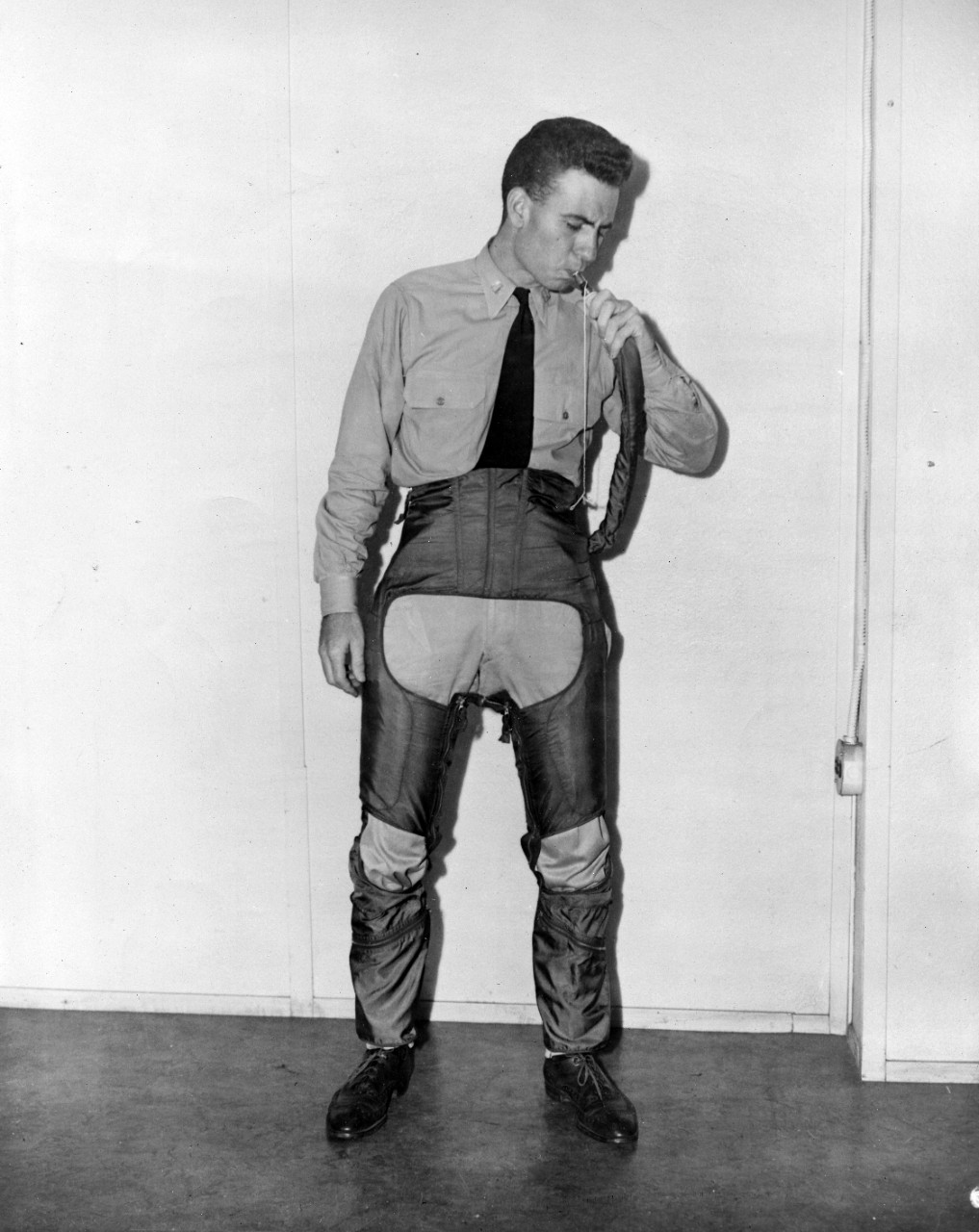 Collection of 20 images related to the naval career of LT Robert Draper Hill. Photos show Hill in various poses modeling the features of the Anti-G suit pants worn by aviators to withstand high g loads during flight. There is also a portrait of Hill in a pilot's leather jacket and uniform. The collection also consists of several official photos from the early 1940s related to aviator training and aircraft, including the N3N (an American tandem-seat, tandem-seat, open cockpit, primary training biplane) at the Naval Air Station Sqantum, MA., as well as several crashes of N2S models at Naval Air Station Memphis, TN. There is a single photograph taken on Johnston Island (Atoll) June, 26, 1944, of the eight men stationed at Zero Tower at the runway. LT Hill was the officer in charge, according to the caption on the reverse of the image.