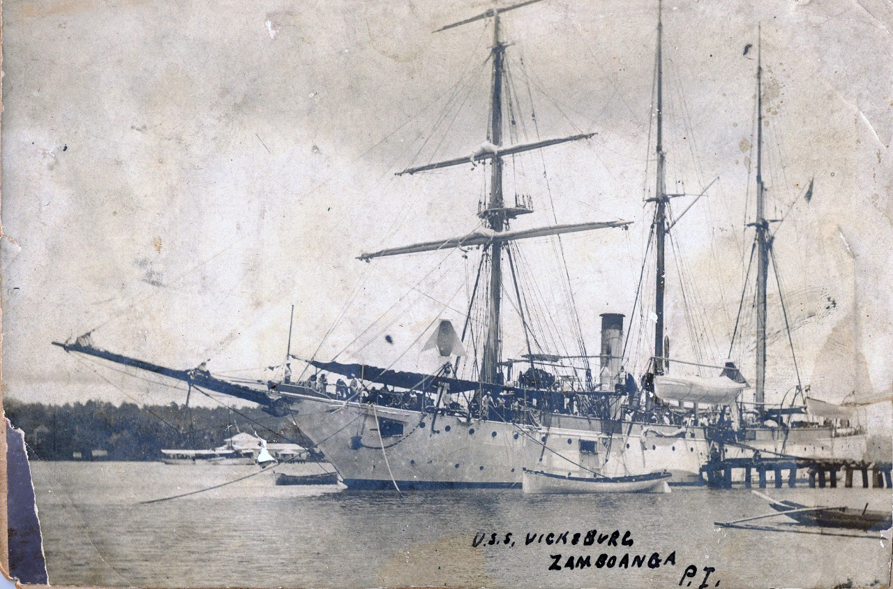 Collection of 6 photos related to USS Vicksburg (PG-11), including in China & the Philippines, circa early 1900s. Specific images include several army officers aboard USS Vicksburg following their capture of Philippine president, Emilio Aguinaldo, at Palanan, Isabela in March 1901; coaling while docked in China; Chinese villagers selling goods in Shanghai, China, and the ship docked in Zamboanga, Philippines.