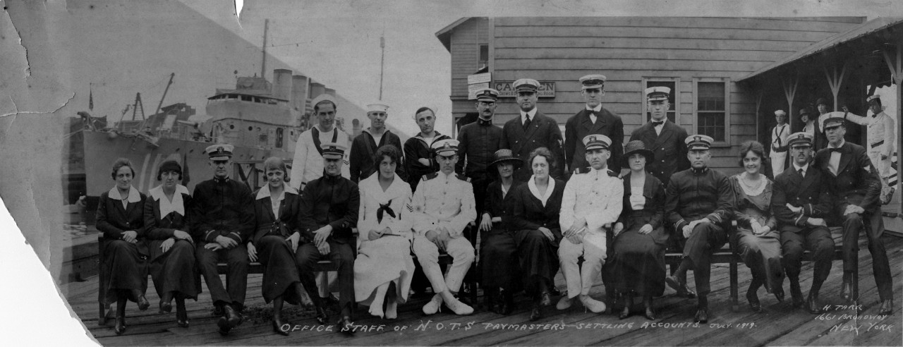 Single oversized image of the office staff and paymasters of the Naval Overseas Transportation Service (N.O.T.S), New York, July, 1919. Photograph taken by H. Tarr. There is damage to the lower left hand side of the photo.
