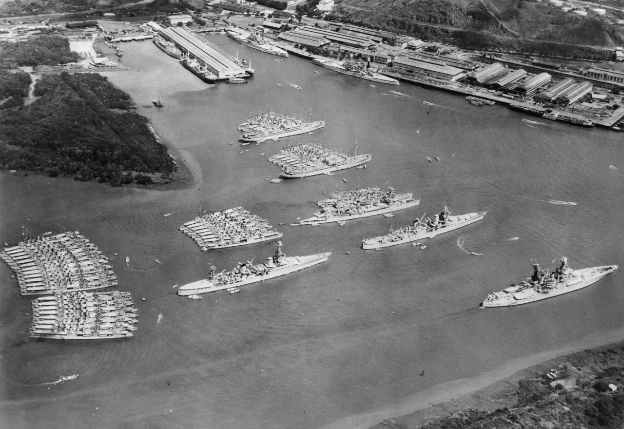 Two black and white images. One shows the Scouting Fleet at Balboa Harbor in the Canal zone,  1934, including USS Indianapolis (CA-35), USS Chicago (CA-29), USS Dobbin (AD-3), USS Whitney (AD-4), USS McFarland (DD-237), USS Goff (DD-247) and other ships including battleships, cruisers, destroyers, and auxiliaries. The other images shows USS Iowa (IX-6, BB-4) under fire as a target in the early 1920's.