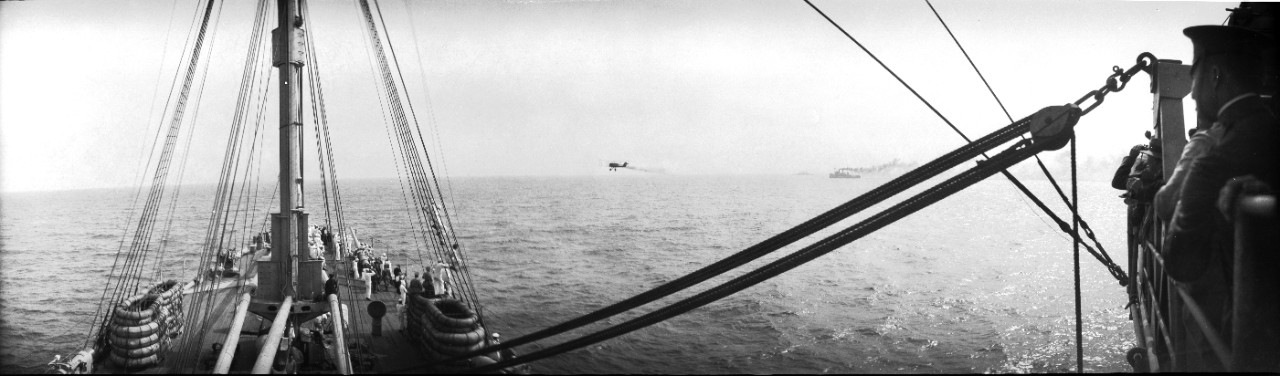 A DH-4 bomber flies low, past the starboard side of USS Henderson (AP-1). Henderson hosted press reporters, military officers, and foreign observers as they observed the 1921 Army-Navy bombing experiments off the Virginia capes.