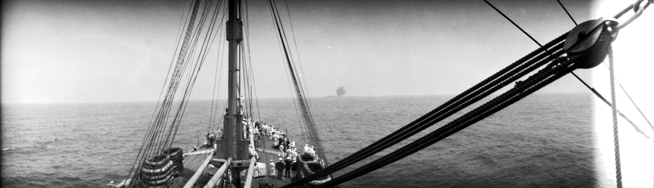 Sailors on board USS Henderson (AP-1) watch as an explosion rocks Ex-SMS Ostfriesland on the horizon, during the 1921 Army-Navy bombing exercises off the Virginia capes.