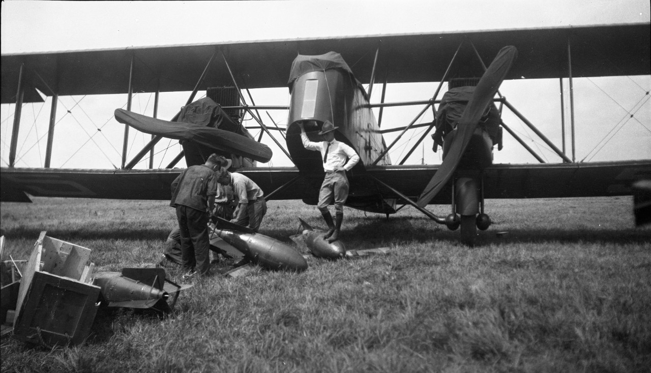 Ground crew loading ordnance on a Martin MB-2 Bomber, circa 1921, likely in support of aerial bombing exercises in conjunction with the Navy.