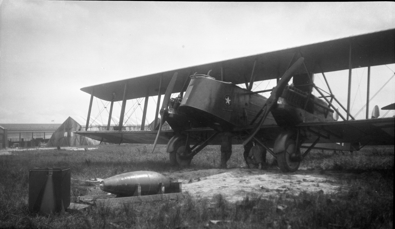 Ground crews inspecting the fuselage of a Martin MB-2 in order to mount ordinance on to the aircraft, circa 1921, likely in support of aerial bombing exercises in conjunction with the Navy.