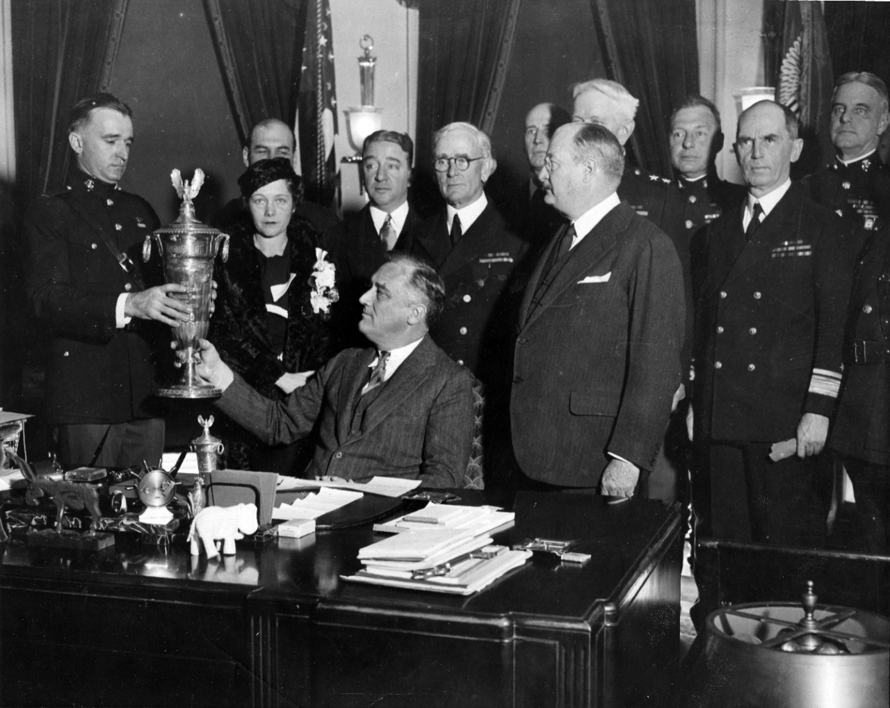 President Franklin D. Roosevelt presents the Herbert Schiff Trophy for naval aviation safety to a Marine aviator, at a ceremony in the White House. At center, standing, is Chief of Naval Operations Admiral William H. Standley. Also seen are Rear Admiral Ernest J. King (standing, center rear) and Rear Admiral William Leahy (at right).
