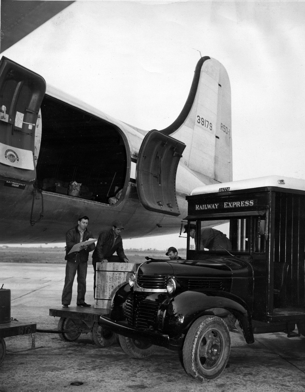 Loading cargo on to a Naval Air Transport Service (NATS) aircraft from a Railway Express vehicle. The crate being loaded is from Honolulu, HI to Naval Air Station Patuxent River, MD, circa 1944.