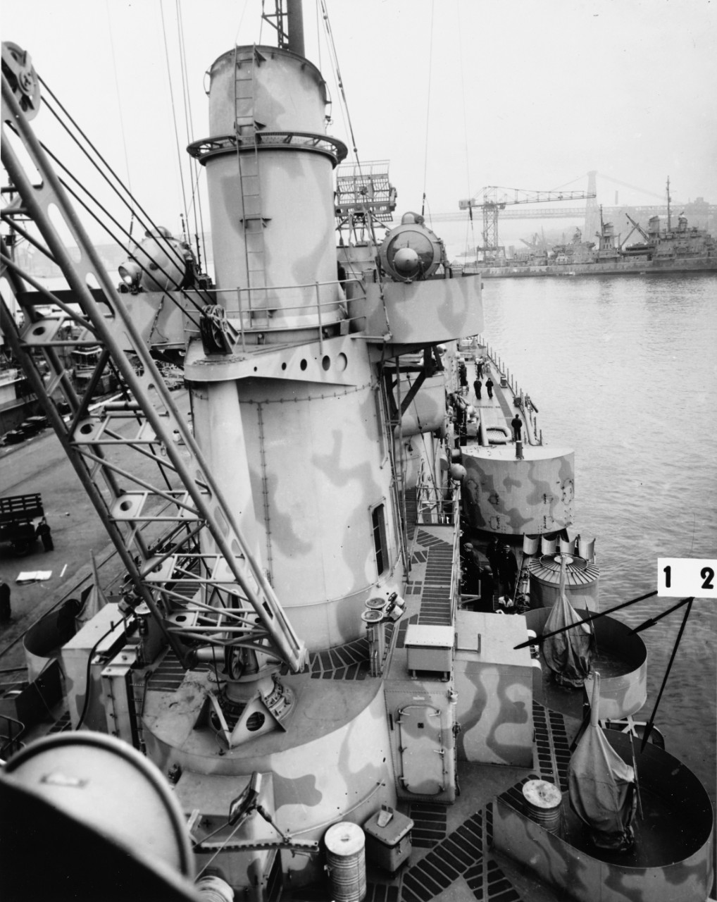 USS Juneau (CL-52) at the New York Navy Yard, 19 March 1942. Arrows mark recent alterations. Note details of boat crane.