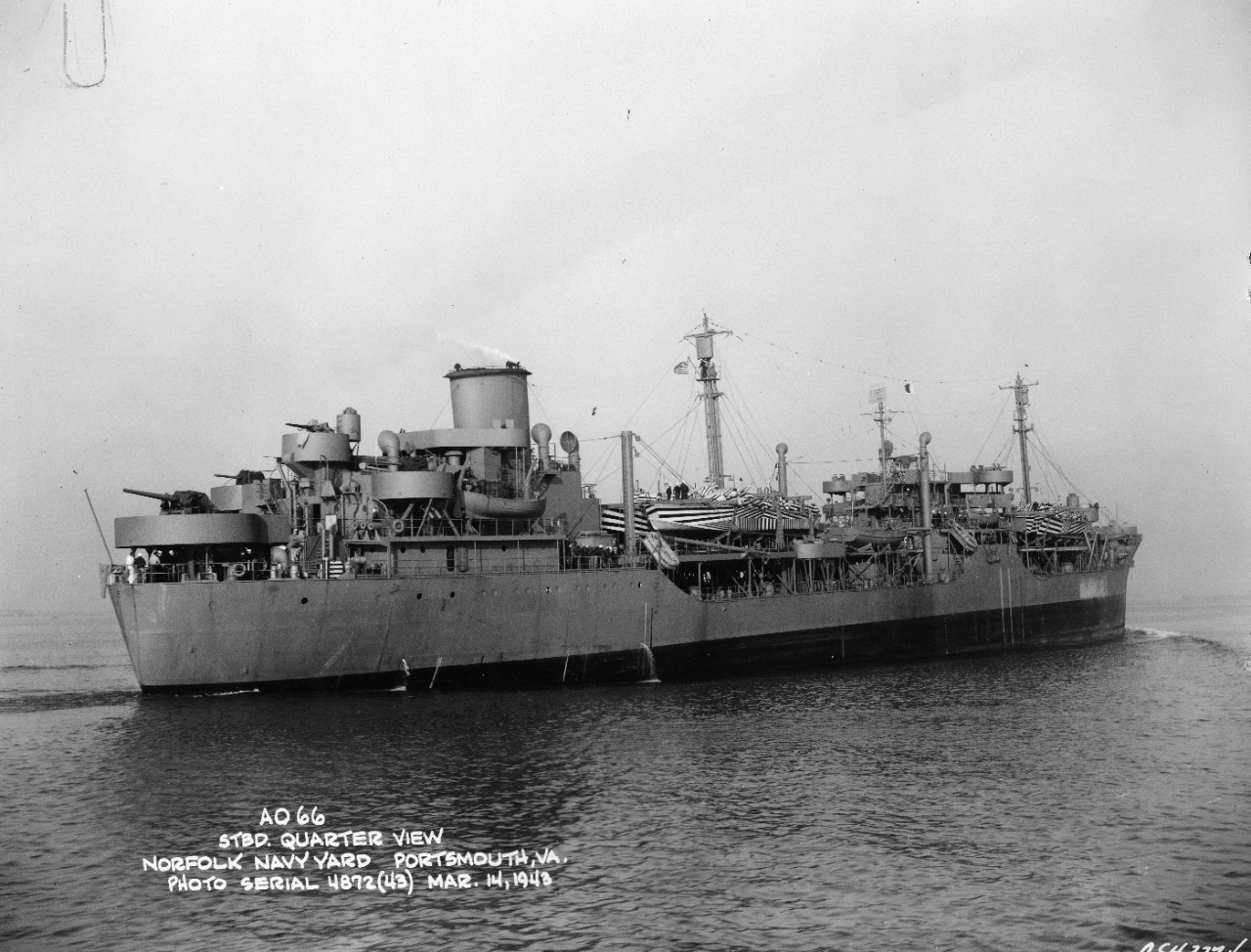 Starboard bow view of USS Atascosa (AO-66) underway in light load condition with camouflaged PT boats as deck cargo fore and aft off the Norfolk Navy Yard, Portsmouth, VA, on 14 March 1943. She was the former S.S. Esso Columbia. Note the lines at her bow. She seems to be streaming paravanes.