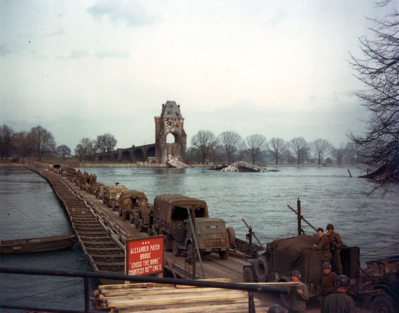 US Army mechanized forces cross the Rhine River on the Alexander Patch Heavy Pontoon Bridge, 28 March 1945. The bridge, built by the 85th Engineers, replaces the ruined bridge at right, which was destroyed by the retreating German Army.