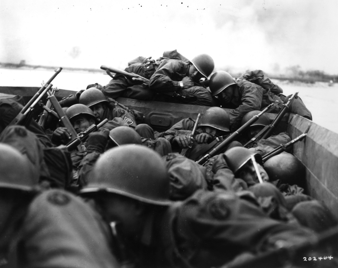 89th Division soldiers crouch low in their crowded assault boat, to escape enemy fire as they cross the Rhine River at Oberwesel, Germany, 26 March 1945. Note 89th Division insignia on men's shoulders, and variety of weapons (including M-1 rifles, Thompson submachine gun, and a Browning Automatic Rifle).